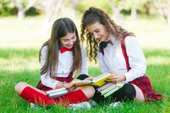 Two schoolgirls in school uniforms sit with books in the park. Schoolgirls or students are taught lessons in nature. Two pretty schoolgirls in school uniforms stock images
