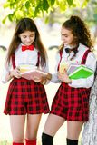 Two schoolgirls in school uniforms stand in a park near a tree with books