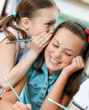 Two schoolgirls whisper to each other. Two funny schoolgirls whisper to each other royalty free stock photography