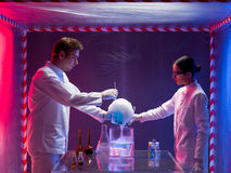 Two scientists experimenting in a containment tent. Two scientists, a men and a woman, mixing chemicals in a containment tent, holding a glass container filled royalty free stock image