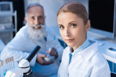 Two scientists in lab coats looking at camera while working. At laboratory royalty free stock image