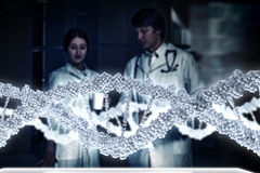 Two scientists in laboratory. Young scientists looking at DNA molecule image at media screen Stock Image