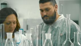 Two scientists measuring liquid in laboratory. The woman wearing protective glasses hold flask in hand and pouring the liquid inside. Laboratory assistant stock footage