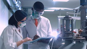 Two scientists with the notepad. Two inspectors with the notepad investigating the factory and writing stock video footage