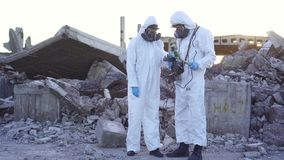 Two scientists in protective suits and masks and make measurements of radiation against the background of the ruins at