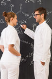 Two scientists standing in front of a blackboard Royalty Free Stock Photo