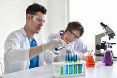 Two scientists are working in laboratory. Young female and male researcher are doing investigations with test tubes Royalty Free Stock Photos
