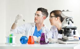 Two scientists are working in laboratory. Young female and male researcher are doing investigations with test tubes Stock Image