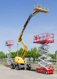 Two scissor and one articulated boom lift on asphalt ground Stock Images