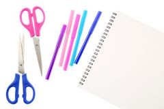 Two scissors, five felt tip pens in pink, blue and purple colors and blank sketchbook, isolated on white background. Space for tex. T on the pad sheet. Art and royalty free stock photo