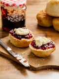 Two scones prepared with clotted cream and jam Stock Image