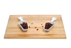 Two Scoops Of Raisins. Shot on a wooden cutting board, all isolated against a white background Stock Photos