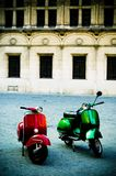 Two Scooters. Two mopeds sitting in a plaza with building in background Royalty Free Stock Photography