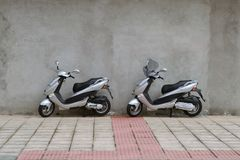 Two scooters parked near the old wall Stock Photos