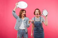 Two screaming women friends holding speech bubbles. Image of two screaming women friends standing isolated over pink background. Looking camera holding speech Royalty Free Stock Images