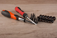 Two screwdrivers and different screws lay on wooden table Royalty Free Stock Image