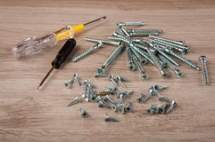 Two screwdrivers and matallic screws lay on wooden table Royalty Free Stock Photos