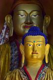 Two sculptures of Buddha in a Buddhist monastery in Zanskar: the yellow figure to the fore, in background is a huge ancient golden Royalty Free Stock Photography