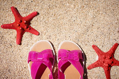 Two sea stars of red color close up on the beach with slates on the sea background in summertime. Concept tourism royalty free stock photography