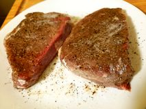 Two seasoned steaks. Two seasoned with salt and pepper steaks on a white plate ready to be cooked Royalty Free Stock Photo