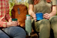 Two seated women hikers pausing for a drink. From a flask with their backpack between them as they enjoy a day hiking in nature Royalty Free Stock Images