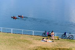 Two two-seater canoes in water and two persons on the beach royalty free stock photography