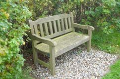 Two seater park bench set on gravel with hedgerow behind. A two seater park bench set on gravel with hedgerow behind royalty free stock photography