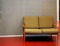 Two-seater retro sofa on red floor. In the background, wallpaper with gray and yellow seamless pattern.  royalty free stock photography