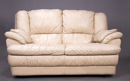Two seater settee. A grubby two seater cream colored leather sofa royalty free stock image