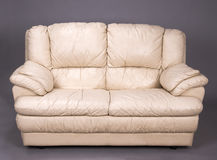 Two seater sofa. A grubby two seater cream colored leather sofa royalty free stock photos