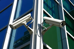 Two security cameras. On glass facade Royalty Free Stock Images
