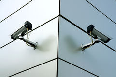 Two security cameras. On the  corner of building Stock Image