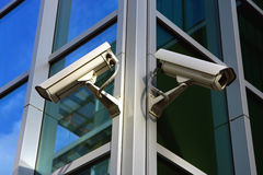 Two security cameras. On cristal facade Royalty Free Stock Photography