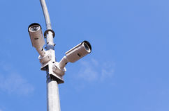 Two security cameras on blue sky royalty free stock image