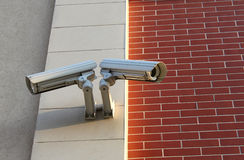 Two security video cameras. On the brick wall Royalty Free Stock Photos