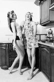 Two seductive beautiful brunette blond young women in apron laughing in kitchen having fun relaxing portrait Royalty Free Stock Images