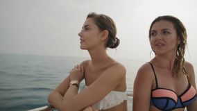 Two seductive young women sitting on the stern of the yacht at sea. Slow motion stock video footage