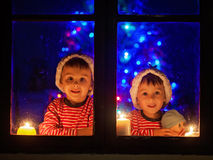 Two seeet boys, sitting on a window, looking outdoor, wintertime Royalty Free Stock Photography