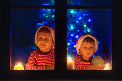 Two seeet boys, sitting on a window, looking outdoor, wintertime Stock Photography