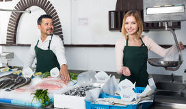 Two sellers in fish section of supermarket Royalty Free Stock Photos