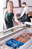 Two sellers in fish store. Portrait of positive male seller and female assistant near display with frozen fish Royalty Free Stock Photography