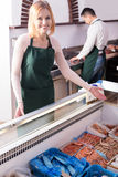 Two sellers in fish store. Portrait of smiling male seller and female assistant near display with frozen fish Royalty Free Stock Image