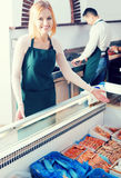 Two sellers in fish store. Portrait of smiling male seller and female assistant near display with frozen fish Stock Photo