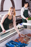 Two sellers in fish store. Positive male seller and female assistant near display with frozen fish Stock Photos