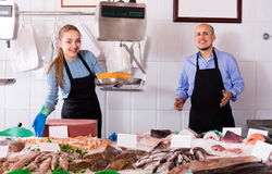 Two sellers in fish store stock image