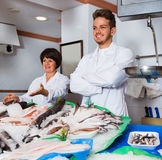 Two sellers posing near display with frozen fish Stock Photography