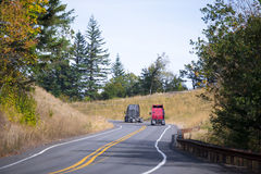 Two semi trucks red and gray tractors on winding road. Two modern comfortable professional semi trucks tractors for transporting long haul cargo moving on the royalty free stock images