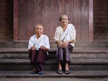 Two senior asian women looking at camera. Portrait of two old asian women sitting on steps out of their house and looking at camera Stock Photos