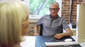 Two Senior Businesspeople Having Meeting In Design Studio. Older businessman and businesswoman sitting either side of desk in modern office having discussion stock video footage