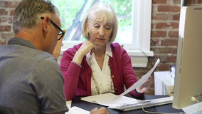 Two Senior Businesspeople Having Meeting In Design Studio. Older businessman and businesswoman sitting either side of desk in modern office discussing paperwork stock footage